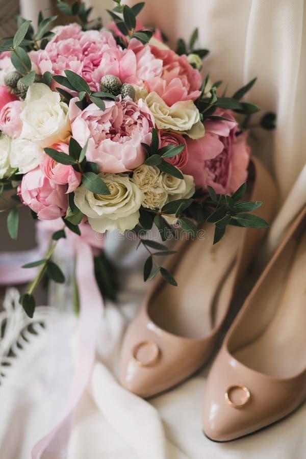 Een huwelijksboeket van roze pioenen, witte rozen, en eucalyptus, naast beige vrouwen` s schoenen royalty-vrije stock foto
