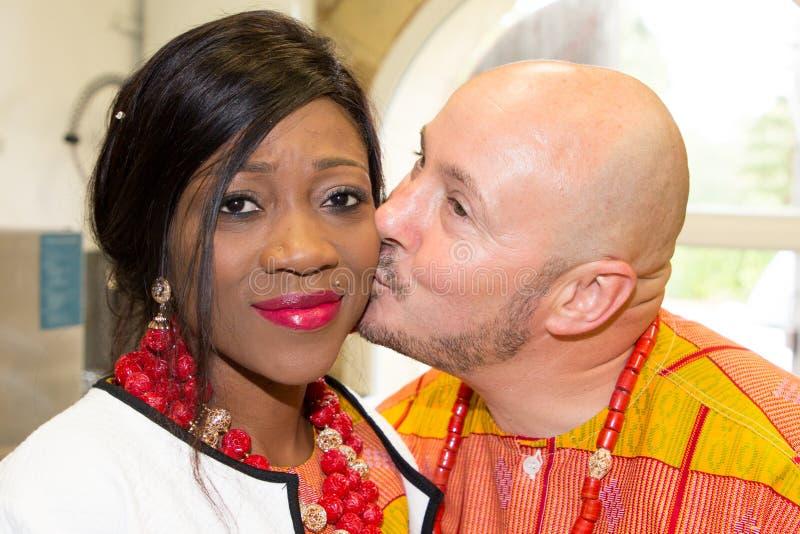 een huwelijkspaar in Afrikaans nationaal kledings traditioneel kostuum en Kaukasische bruidegom royalty-vrije stock foto