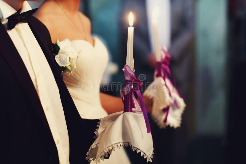 Een huwelijkspaar houdt kaarsen met violette linten tijdens een eng stock fotografie
