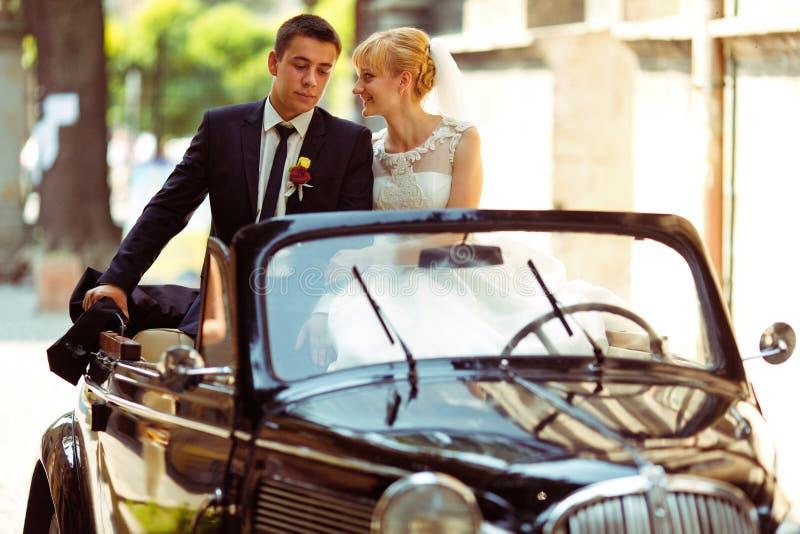 Een huwelijkspaar zit op zwarte retro cabriolet royalty-vrije stock afbeelding