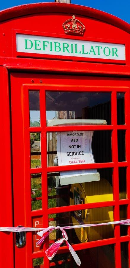 Een Iconische Britse publieke telefooncelcabine zette in een defibrillator post om stock afbeeldingen