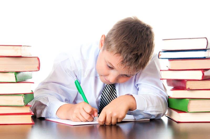 Een ijverige jongen van de middelbare schoolstudent zit in een bibliotheek met boeken en leert lessen, schrijft thuiswerk Examenv royalty-vrije stock fotografie