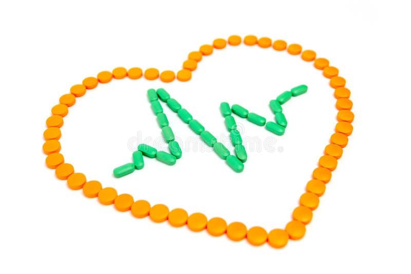 Een impuls is door groene pillen in het oranje die hart op witte achtergrond wordt geïsoleerd Het concept van de geneeskunde royalty-vrije stock afbeelding