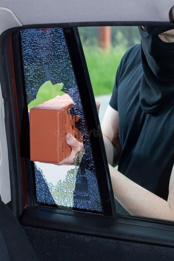 Een inbreker breekt een venster in de auto royalty-vrije stock fotografie