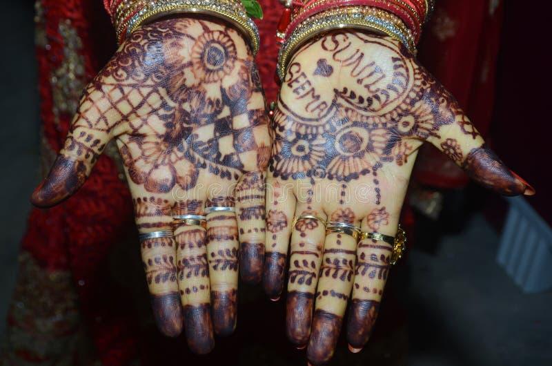 Een Indische bruidegom die haar hand met het mooie mehndi desing toont tijdens huwelijk stock foto's