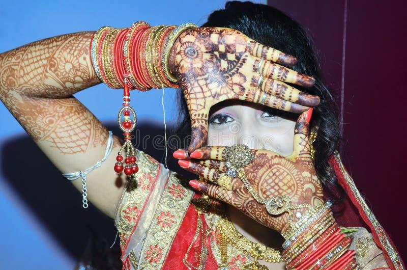 Een Indische bruidegom die haar ogen van haar handontwerp toont royalty-vrije stock foto