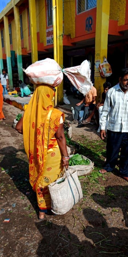 Een Indische dorpsvrouw droeg plantaardige zak op hoofd in de landelijke marktstraat royalty-vrije stock foto's