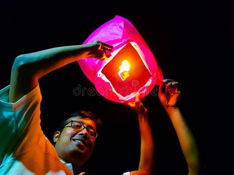 Een Indische mens die een aangestoken document hete luchtballon in het festival van de hemellantaarn vrijgeeft royalty-vrije stock foto