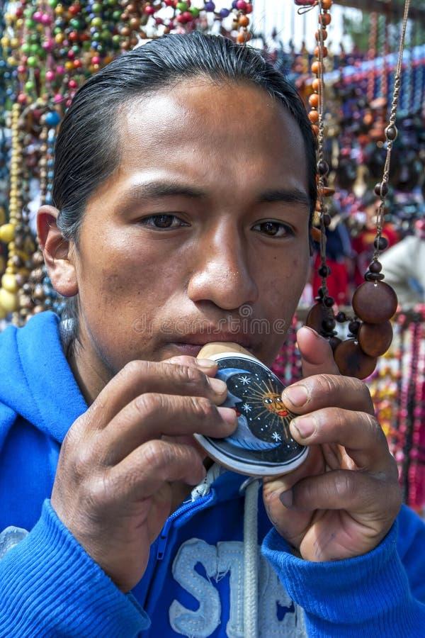 Een Indische mens die een kleurrijke fluit spelen bij de Indische Markt in Otavolo in Ecuador stock afbeeldingen