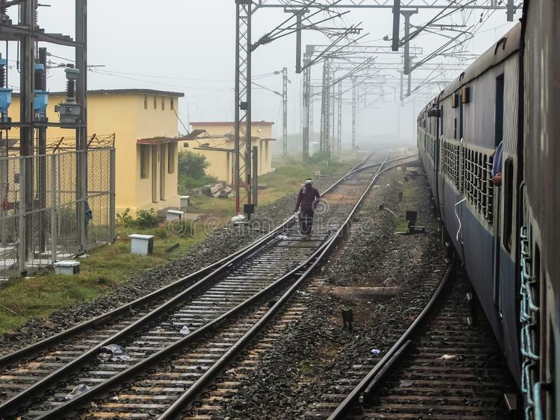 Een Indische mens die op de spoorwegsporen lopen Mening van de trein royalty-vrije stock fotografie