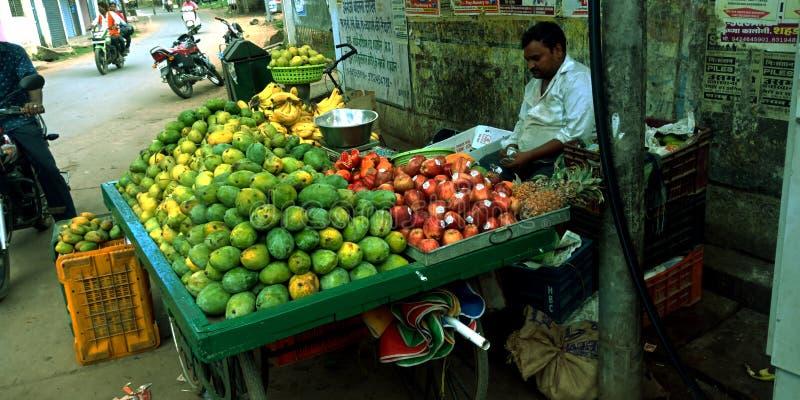 Een Indische verkoper van het dorpsfruit bij lokaal gebied stock foto