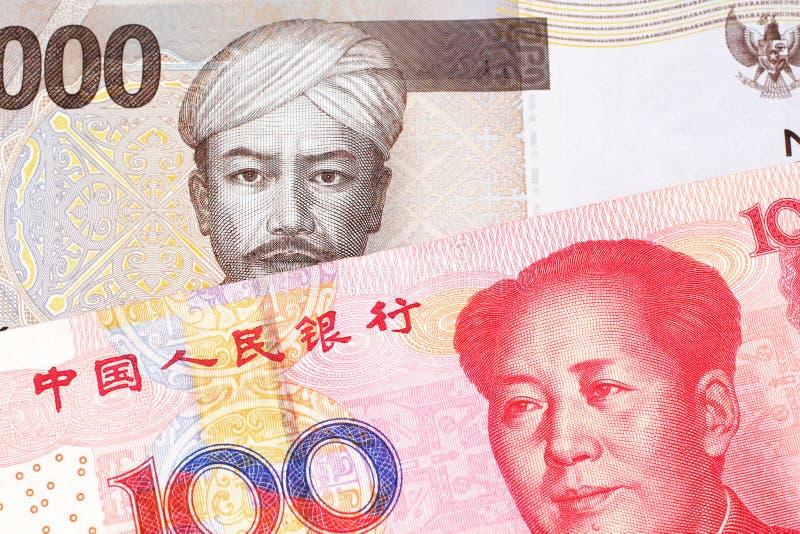 Een Indonesisch Roepiebankbiljet met een Chinese honderd yuansrekening royalty-vrije stock afbeelding