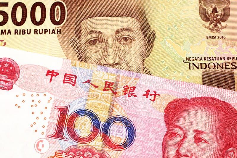 Een Indonesisch Roepiebankbiljet met een Chinese honderd yuansrekening stock fotografie