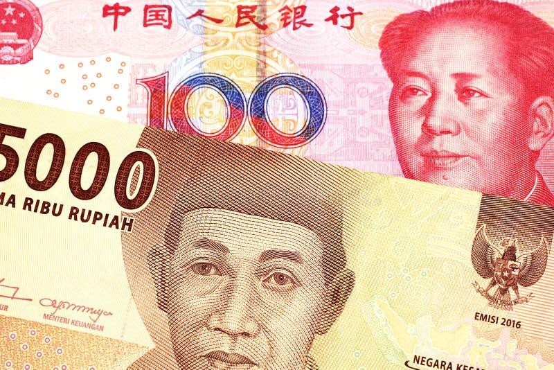 Een Indonesisch Roepiebankbiljet met een Chinese honderd yuansrekening stock afbeeldingen