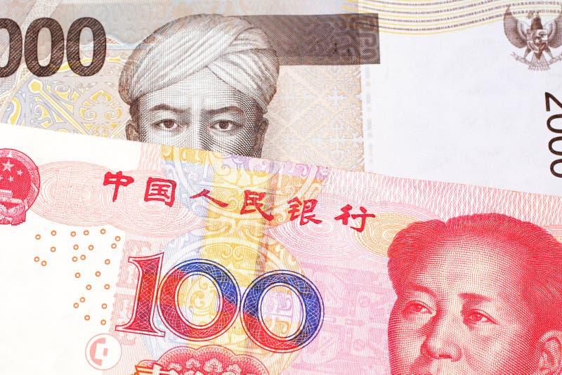 Een Indonesisch Roepiebankbiljet met een Chinese honderd yuansrekening royalty-vrije stock fotografie