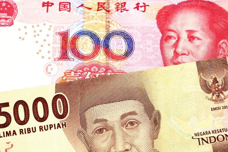 Een Indonesisch Roepiebankbiljet met een Chinese honderd yuansrekening royalty-vrije stock foto's