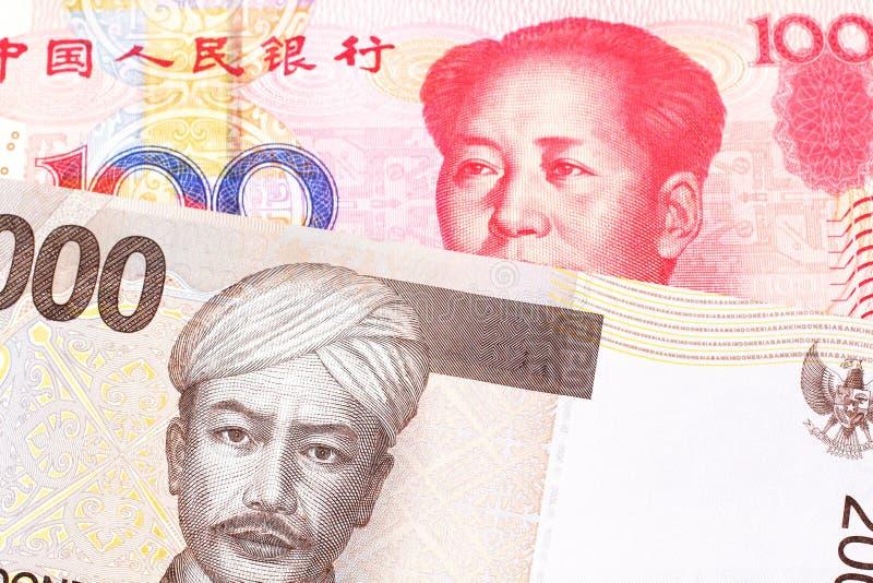 Een Indonesisch Roepiebankbiljet met een Chinese honderd yuansrekening stock foto