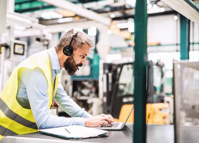 Een industriële menseningenieur met hoofdtelefoon en laptop in een fabriek, het werken royalty-vrije stock afbeelding
