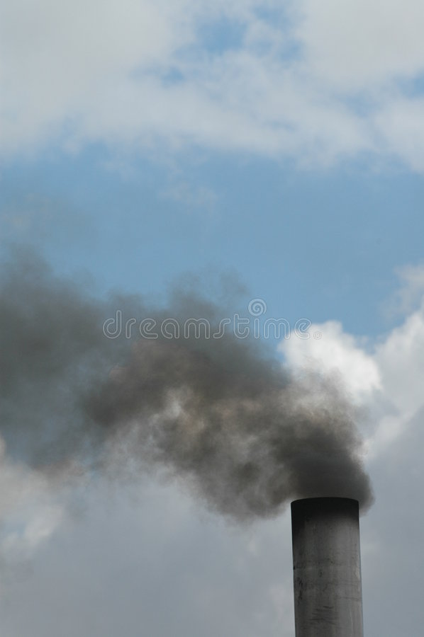 Een industriële rokende schoorsteen stock afbeeldingen