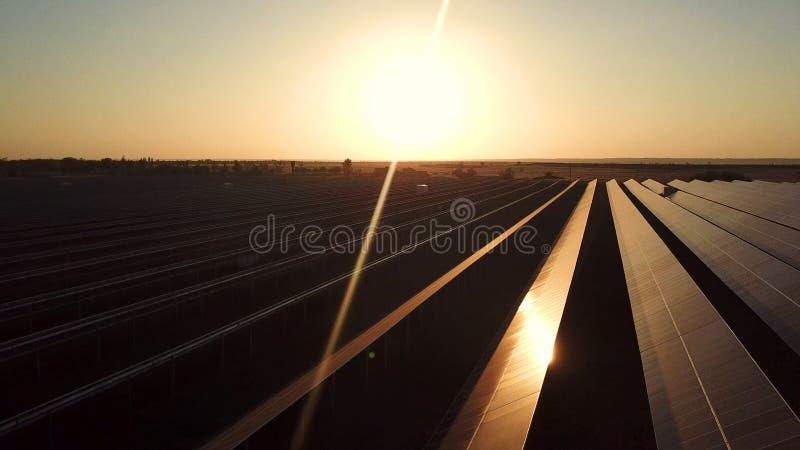 Een industrieel zonne-energielandbouwbedrijf bij zonsondergang royalty-vrije stock foto's