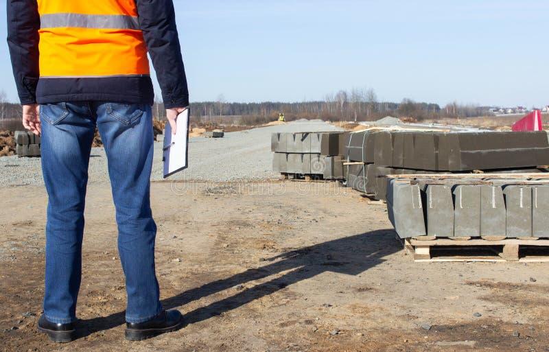 Een ingenieur met een omslag in het signaalvest controleert de kwaliteit van de rand het aanleggen van een nieuwe weg, inspecteur royalty-vrije stock foto's