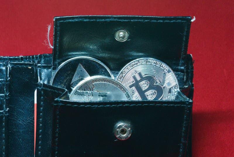 Een inzameling van gouden en zilveren cryptocurrencymuntstukken in een portefeuille royalty-vrije stock afbeelding