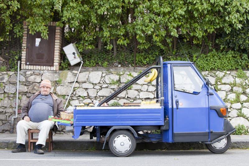 Een Italiaanse straatventergroentehandelaar Oude blauwe auto royalty-vrije stock afbeeldingen