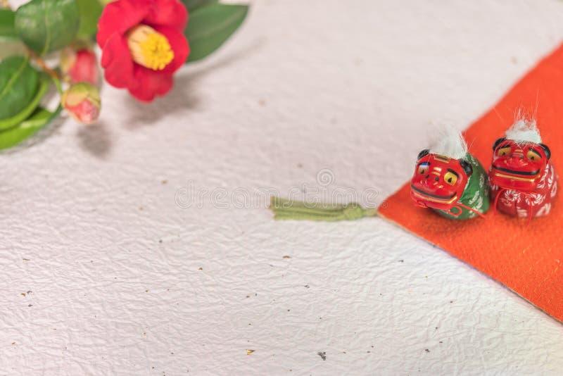 Een Japanse wenskaart met een Tsubaki-bloem die ook de winterroos en twee Folklore-dierfiguren heet royalty-vrije stock afbeeldingen