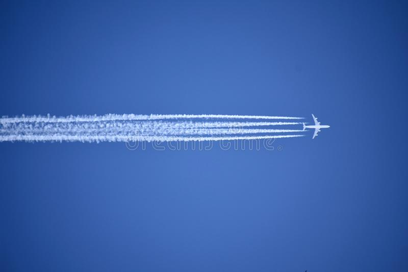 Een jet die boven verlaat vier condensatieslepen tegen een levendige, blauwe hemel vliegen royalty-vrije stock foto's