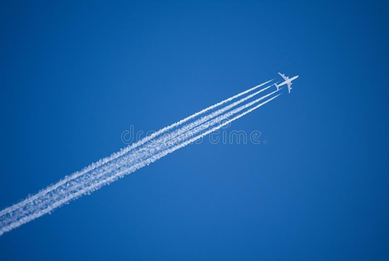 Een jet die boven verlaat vier condensatieslepen tegen een levendige, blauwe hemel vliegen stock afbeeldingen
