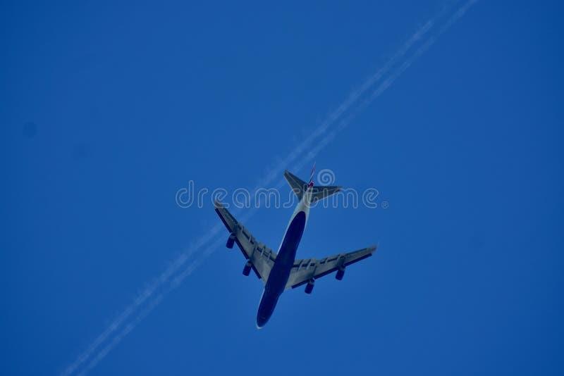 Een jet die onder een blauwe hemel vliegen stock fotografie
