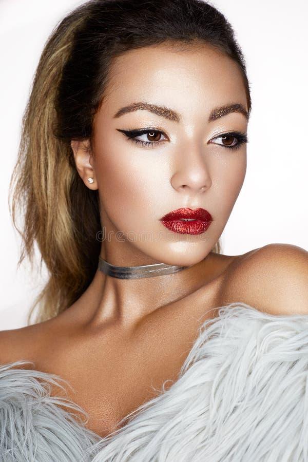 Een jong Aziatisch meisje met creatieve make-up, pijlen en heldere rode lippen met fonkelingen Een mooi model met perfecte huid i stock afbeeldingen