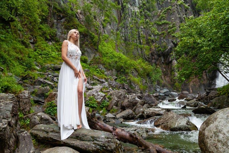 Een jong blond meisje in elegant stelt bares haar been terwijl het doen leunen van de boord van een boudoirkleding, in de bergen  stock afbeeldingen