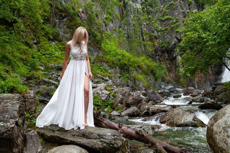 Een jong blond meisje in elegant stelt bares haar been terwijl het doen leunen van de boord van een boudoirkleding, in de bergen  royalty-vrije stock afbeeldingen