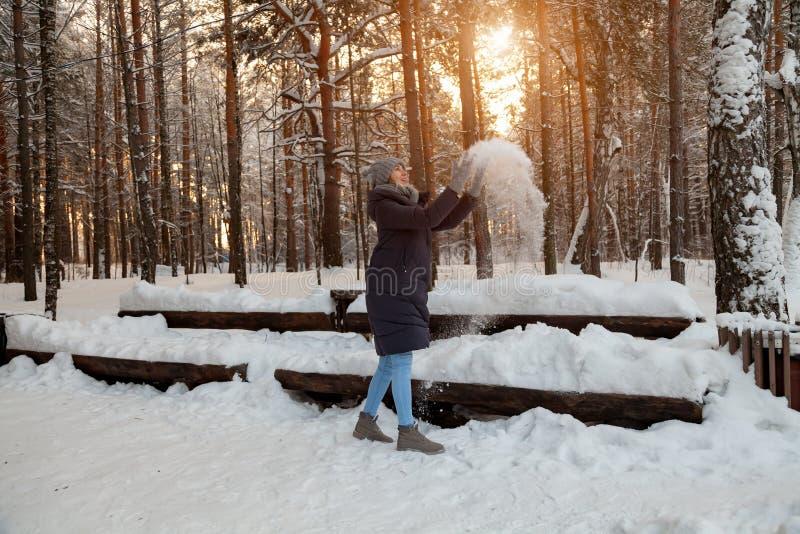 Een jong blondemeisje in de winter naald bostribunes in een grijze hoed en handschoenen en een donkerblauw jasje die omhoog werpe stock afbeelding