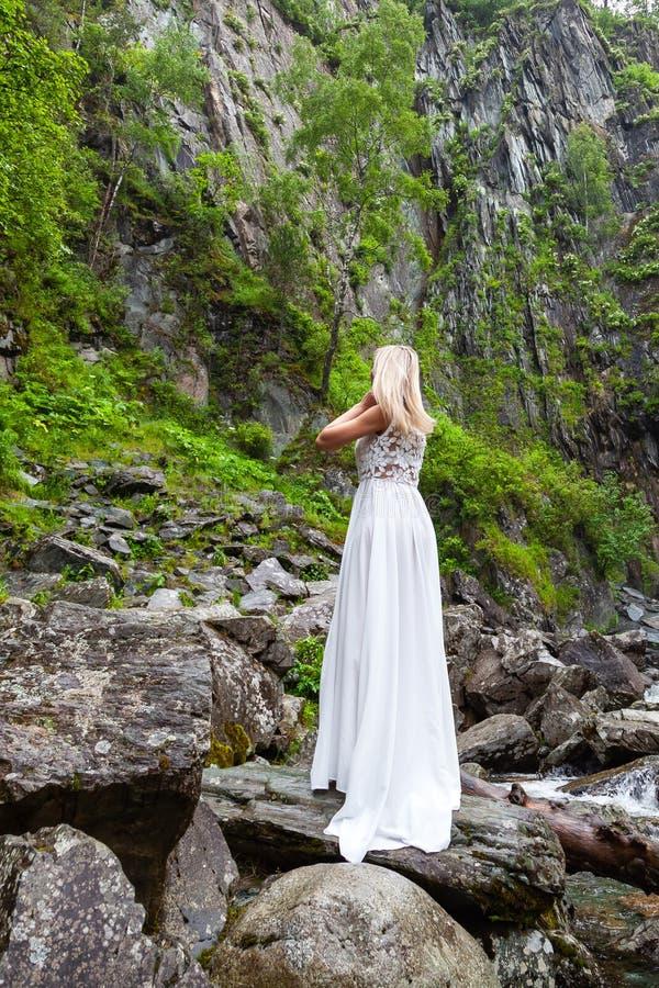 Een jong blondemeisje die zich met haar terug in een witte boudoirkleding in de bergen tegen een achtergrond van een waterval bev royalty-vrije stock foto