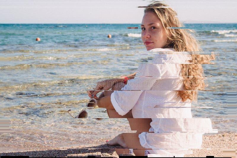 Een jong blondemeisje in een wit peinzend overhemd zit op het strand in Egypte Exotische schoonheid Een hoge resolutie Glitch sjo stock fotografie
