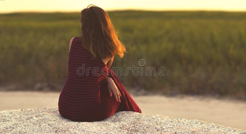 Een jong droommeisje dat op het zand zit en kijkt naar de afstand op het veld aan de horizon, een vrouw die geniet van de zonsond royalty-vrije stock afbeelding