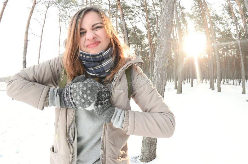 Een jong en blij Kaukasisch meisje in een bruine laag beeldhouwt een sneeuwbal in een snow-covered bos in de winter Spelen met sn stock fotografie