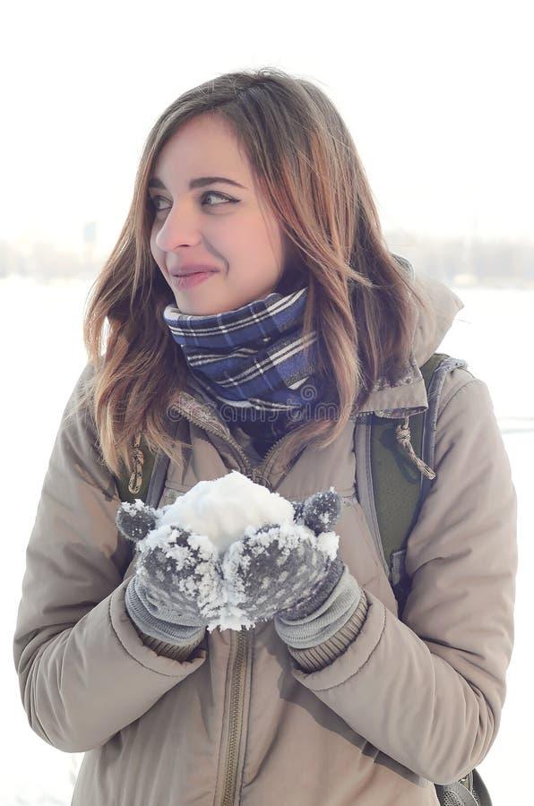 Een jong en blij Kaukasisch meisje in een bruine laag houdt een sneeuwbal op de achtergrond van een horizonlijn tussen de hemel e royalty-vrije stock afbeelding
