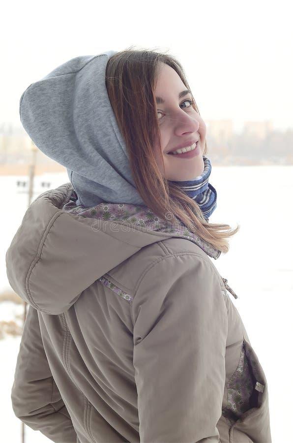 Een jong en glimlachend Kaukasisch meisje kijkt rond de horizonlijn tussen de hemel en het bevroren meer in de wintertijd royalty-vrije stock afbeeldingen