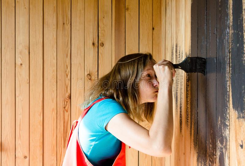 Een jong en mooi meisje met een leeswijzer in haar handen was zeer geconcentreerd bij het schilderen van de houten oppervlakte in royalty-vrije stock afbeelding
