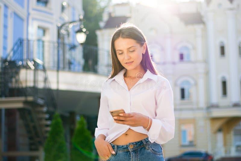 Een jong, fashionably gekleed meisje met een smartphone op een stad st stock afbeeldingen