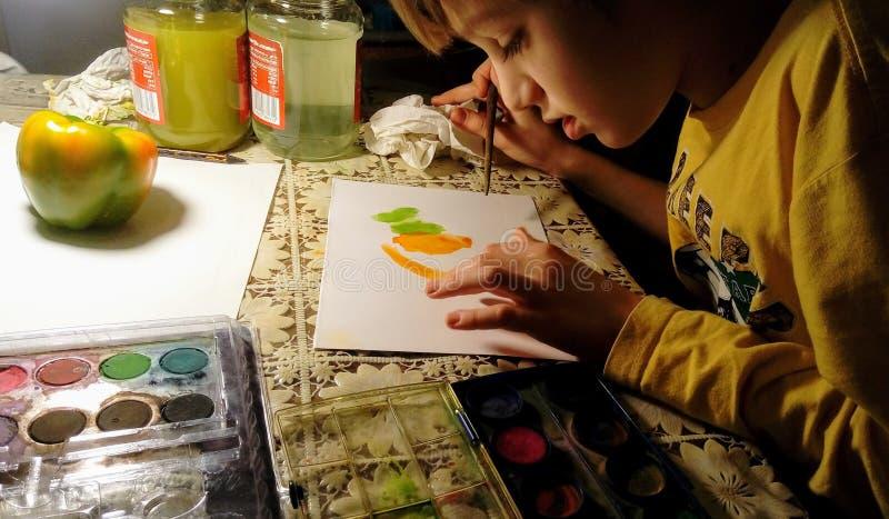 Een jong geitje trekt een groene en gele groene paprika met een verf in de avond royalty-vrije stock afbeelding