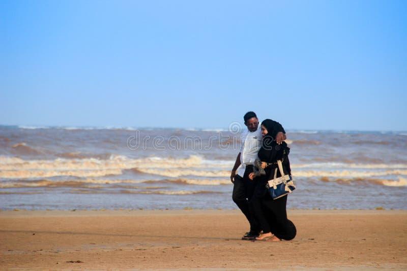 Een jong gelukkig Moslim zwart paar loopt langs de kust van de Indische Oceaan royalty-vrije stock afbeelding