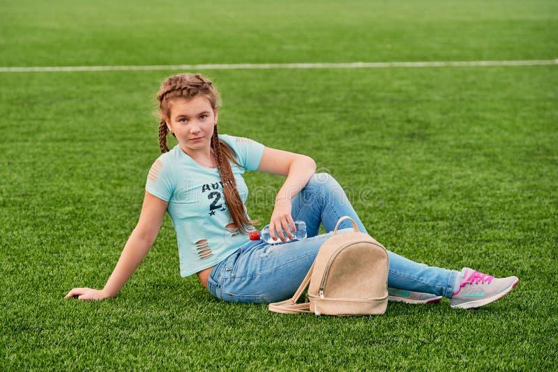 Een jong helder meisje houdt van sporten de zitting van het tienermeisje op het schoolgebied stock afbeelding