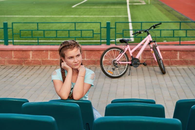 Een jong helder meisje houdt van sporten Het meisje in de blauwe zetels van het stadion stock afbeeldingen