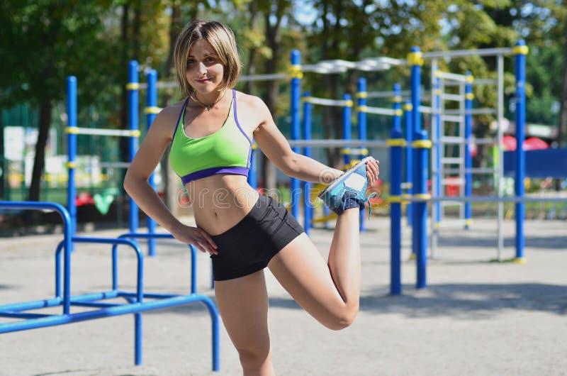 Een jong Kaukasisch atletenmeisje in een heldergroene sportkleding doin stock afbeelding