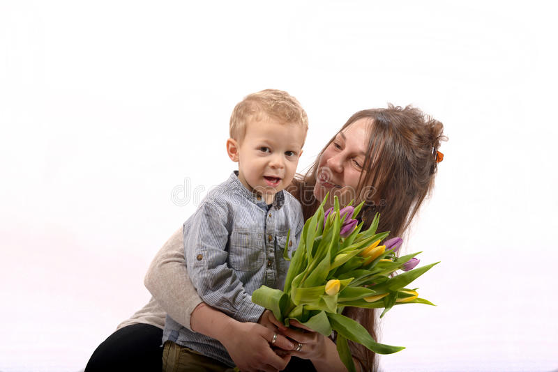Een jong kind biedt bloemen aan zijn mamma aan stock fotografie