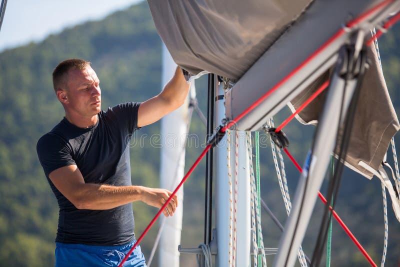 Een jong mannelijk zeeman het plaatsen zeil op zijn jacht Sport stock afbeelding